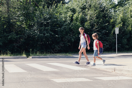 Leinwand Poster Girl and boy with backpacks walking on pedestrian crossing from the school