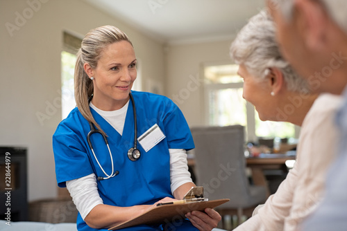 Friendly nurse talking with old couple