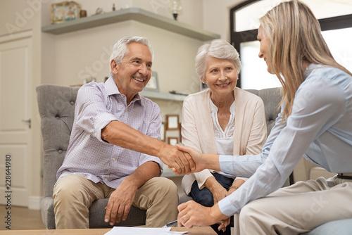 Fototapeta Senior couple shaking hands with financial advisor obraz