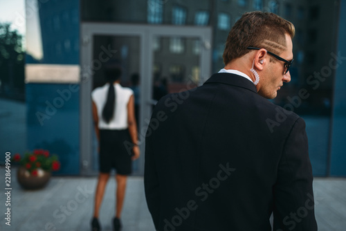 Personal guard in sunglasses and security earpiece