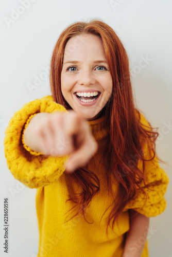 Laughing young redhead woman pointing at camera