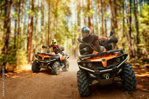 Poster Motorise Two atv riders, speed race in forest, front view
