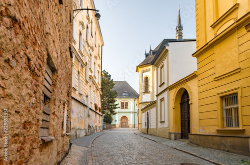 Poster Smal steegje Cobblestone street cityscape with baroque and dilapidated buildings in the old town of Olomouc, Czech Republic.