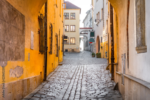 Canvas Prints Narrow alley Narrow cobblestone street leading upwards flanked by historical buildings in the old town of Olomouc, Czech Republic
