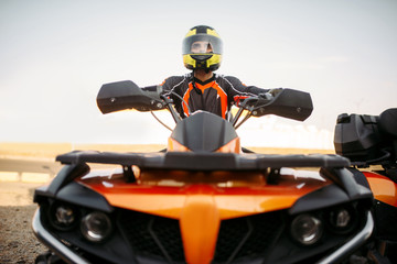 Rider in helmet on quad bike, front view, closeup