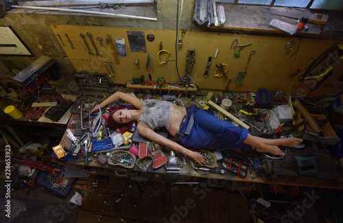 Obraz A young beautiful woman finds time to relax during  her working hours. She lies down on the work bench filled with tools and other electronic devices. - fototapety do salonu