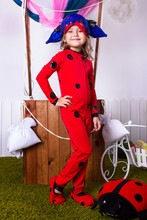 Little Girl In Ladybug Overalls. Kid Christmas Halloween Costume. Young Girl Superhero In White Room Is Standing  Near Basket With A Balloon And Toy Ladybug On The Grass On The White Wall Background