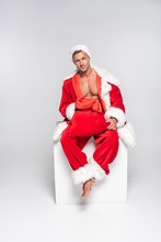 Sexy Man In Santa Costume Sitting With Red Bag And Looking At Camera On Grey