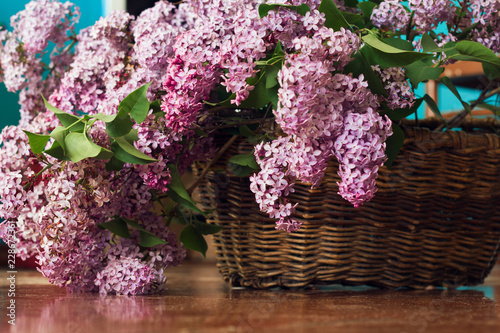 Fotobehang Lilac Lilac flowers bunch in a vintage brown basket