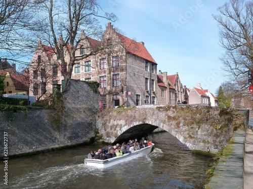 Groenerei à Bruges, canal avec une barque de touristes passant sous un vieux pont (Belgique)