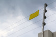 high electric fence with blank yellow sign, security fence for house in cloudy day.