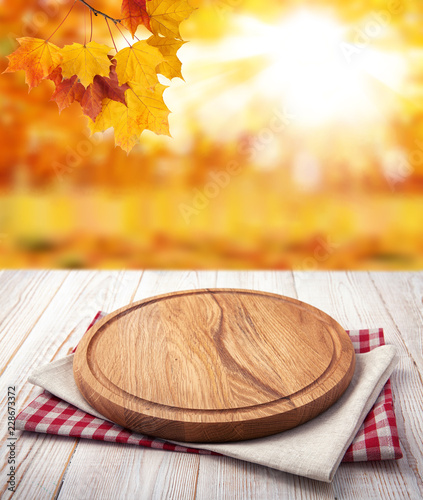Autumn landscape and pizza board with napkin on wooden table. Top view mock up