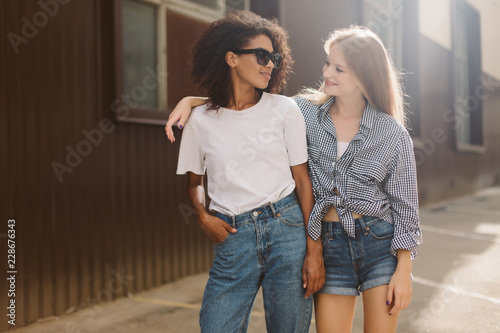 Fotografía  Young african american woman with dark curly hair in sunglasses and T-shirt and