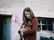 Smiling Brunette Woman Holding Chicken In Her Arms