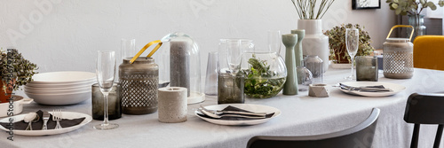Panorama of grey table with wine glasses, candles and tableware in dining room interior. Real photo