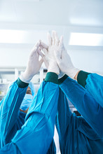 Hands Of Crop Surgical Team In Gloves Giving High-five To Each Other Before Performing Surgery In Modern Operating Theatre