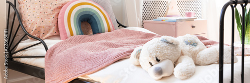 Obraz Close-up of child bed with teddy bear, pastel pink blanket and rainbow cushion in the real photo - fototapety do salonu