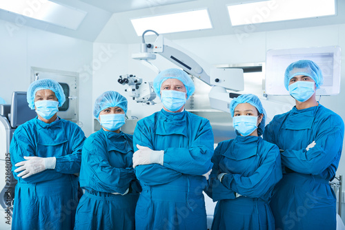 Fotografía Asian surgical team in masks and uniform keeping arms crossed and looking at cam