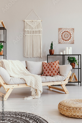 Photo Blanket and cushion on couch in boho living room interior with pouf and poster