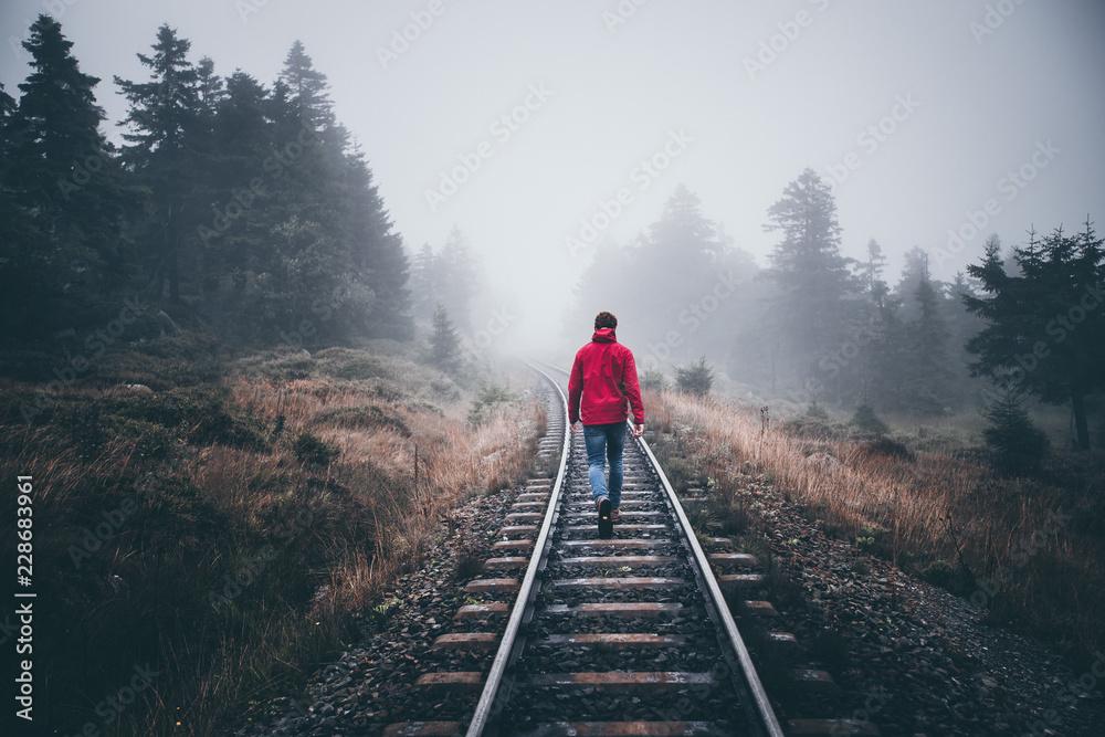 Fototapety, obrazy: Wanderer läuft in roter Jacke über Schienen im Harz