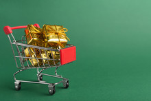 Shopping Cart With Golden Christmas Gifts Over Green Background