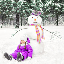 Child And Snowman In A Snow-covered Park. Winter Outdoor Activities