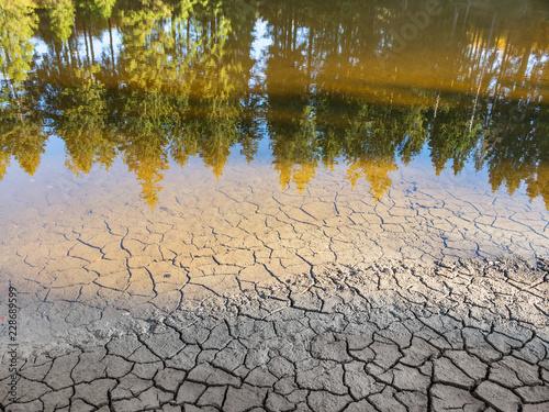 Niedriger Wasserstand in einem See aufgrund anhaltender Trockenheit Fototapete