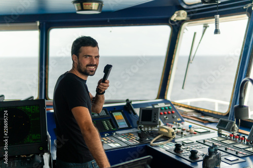 Carta da parati  Marine navigational officer is reporting by VHF radio during navigation watch