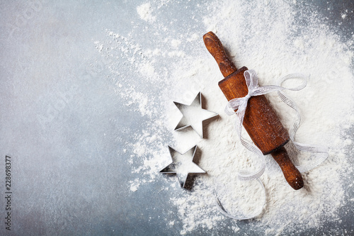 Bakery background for cooking christmas baking with rolling pin and scattered flour on kitchen table top view.