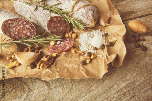 Stickers pour porte Pierre, Sable Italian salami wih sea salt, rosemary, garlic and nuts on paper. Rustic style. Top view.