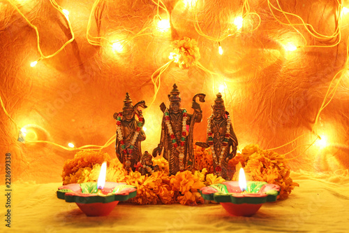 hindu god ram, sita, laxman, hanumaan statue with decorative lights, oil clay lamps and flowers for diwali celebration