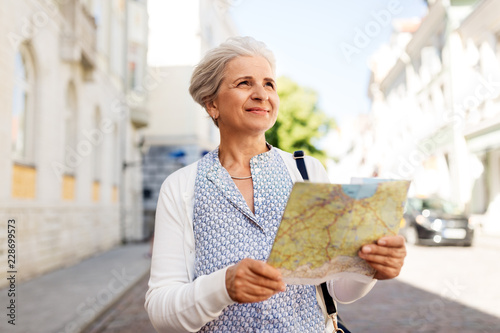travel, tourism and retirement concept - senior woman or tourist with map on cit Canvas