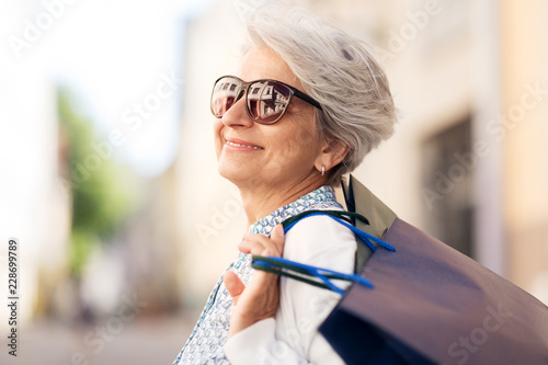 Fototapeta sale, consumerism and people concept - senior woman in sunglasses with shopping bags in city obraz