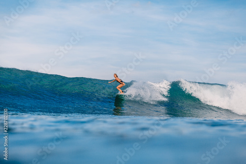 Professional surf girl at surfboard ride on barrel wave Canvas Print