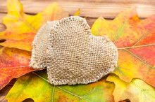 Burlap Heart With Autumn Leaves On Wooden Table. Close Up.