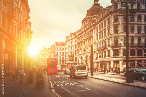 Foto op Canvas Londen rode bus Oxford Street in London against golden sun ray while after work