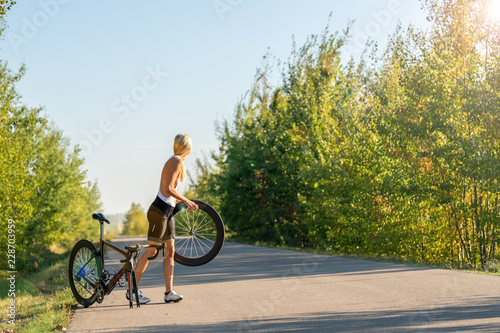 Foto op Aluminium Fietsen Sexy girl with a road bike and a flat tire looking for help