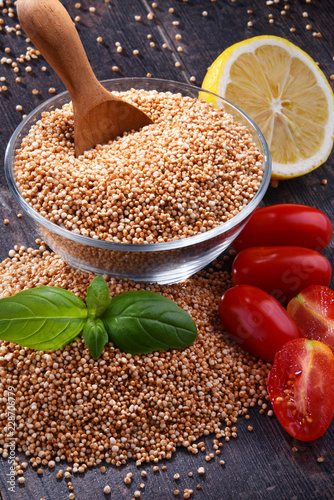 Bowl of amaranth grain on wooden table Wallpaper Mural