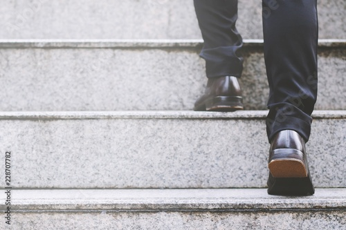 Close up legs shoes of young business man One person walking stepping going up the stairs in modern city, go up, success, grow up. with filter Tones retro vintage warm effect. stairway - fototapety na wymiar