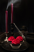 A Halloween Centerpiece Of Three Chocolate Cupcakes On A Spiderweb Plate With Small Cauldron Bowls, Spiderwebs And Two Candles With Smoke Billowing Out The Top With A Solid Black Background