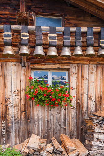 Fotografia  old cow bells under the roof of an Alpine mountain hut, Switzerland