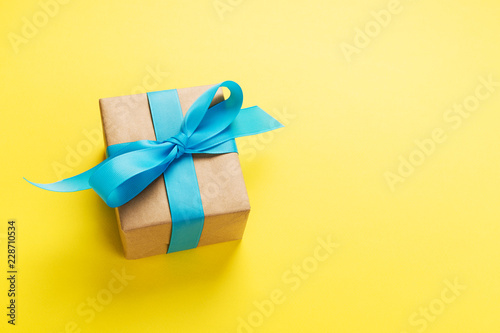 Photo  gift wrapped and decorated with blue bow on yellow background with copy space