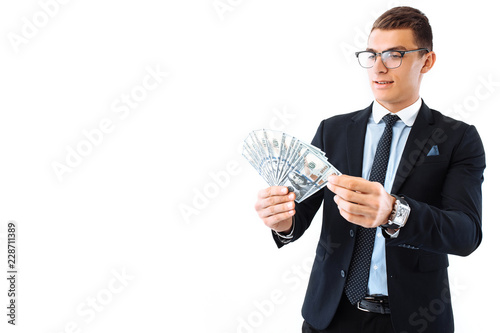 Vászonkép A successful businessman in glasses and a suit, holding dollar bills, carefully recalculates them on a white background