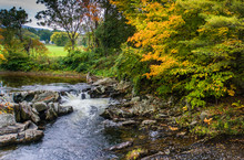 Water Flowing Over Rocky Creek Bed With Golden Hues Of Fall Autumn Foliage