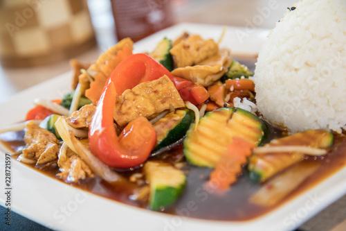Photo  Vegetarisch Tofu Gemüse aus Wok mit pikanter, brauner Szechuan Soße und Reis im