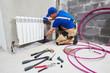 Leinwanddruck Bild - plumber at work. Installing water heating radiator