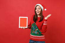 Surprised Young Santa Girl Spreading Hands, Holding Tablet Pc Computer With Blank Empty Screen Isolated On Red Background. Happy New Year 2019 Celebration Holiday Party Concept. Mock Up Copy Space.