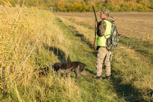 Foto op Aluminium Jacht Hunters with a german drathaar and spaniel, pigeon hunting with dogs in reflective vests