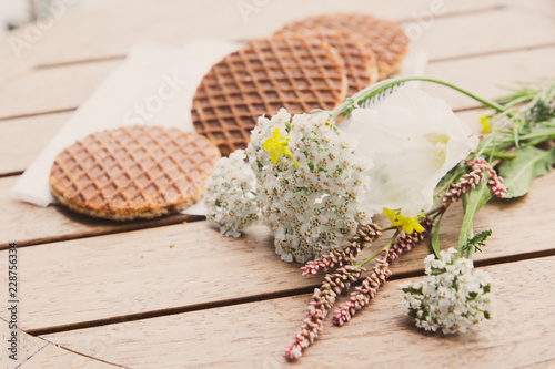 Traditional Dutch Stroopwafels syrup filled waffle cookies in setting with flowers