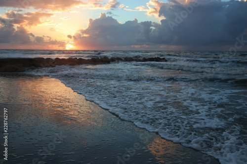 Deurstickers Ochtendgloren Sunrise over the beach with rocks and waves